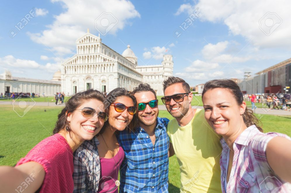 Group of tourists or friends taking a selfie in Pisa, Italy, with famous leaning tower on background. They are two men and three women. Lifestyle, friendship and travel concepts.