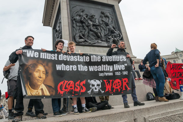 "The National Campaign Against Fees & Cuts banner at the rally in Trafalgar Square is soon joined by Class War's Lucy Parsons banner with its quotation ""We must devastate the avenues where the wealthy live."""